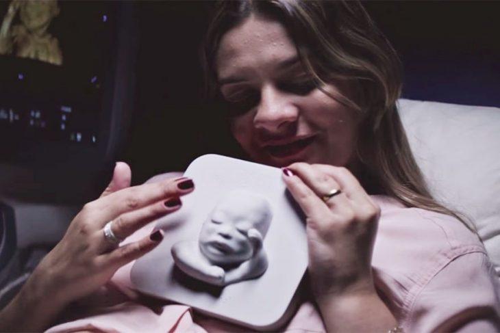 madre acariciando al busto impreso en 3D de un bebé