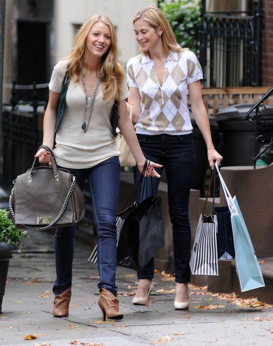 madre e hija caminando por la calle con bolsas de compras en las manos