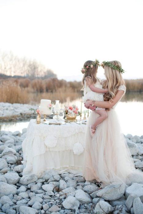 madre e hija junto a la playa con un pastel en una mesa
