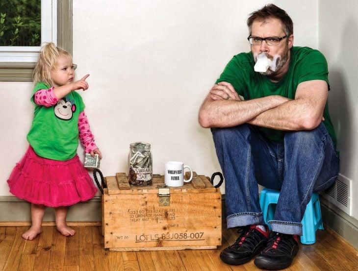 hombre sentado en un banco comiendo jabón mientras su hija lo regaña