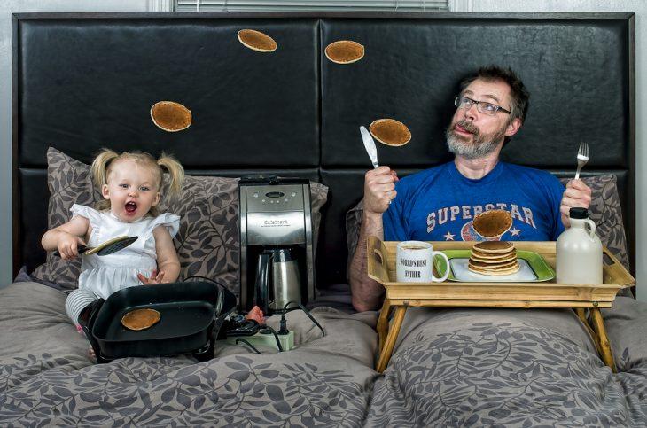 niña y su papá comiendo hotcakes en la cama