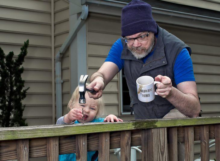 hombre clavando un clavo en una cerca mientras su hija sostiene el clavo