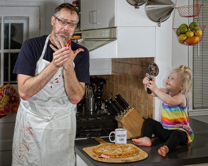niña cortandole un dedo a un hombre con un cuchillo de pizza