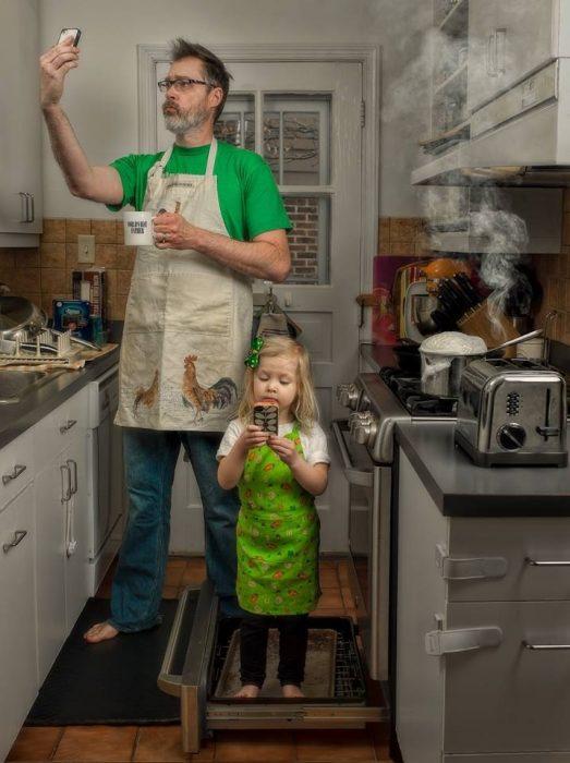 hombre y niña tomando una selfie en la cocina
