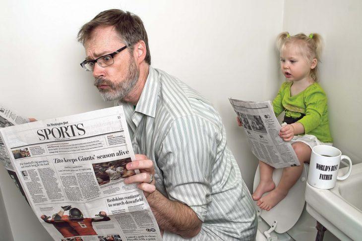 hombre sentado en el baño leyendo el periódico