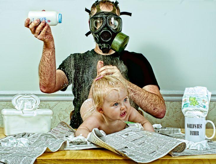 hombre usando una mascara anti-gas para cambiar los pañales a su bebé