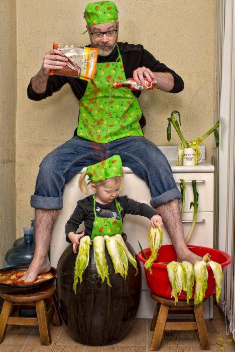 hombre cocinando a una niña con verduras y especias