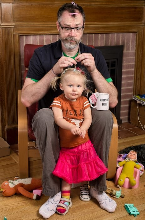 hombre peinando a una niña con trenzas