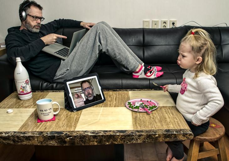 hombre con una computadora en los pies mientras una niña ve una tablet en una mesa