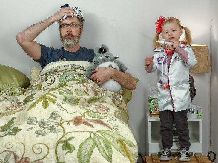 hombre en la cama curandose la fiebre mientras su hija le toma la temperatura