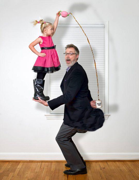 niña parada en las manos de su papa mientras ella le sirve café tras la espalda