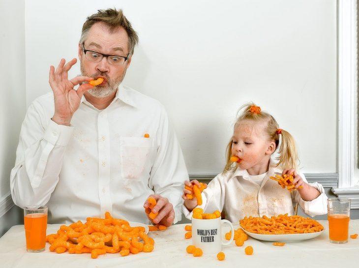 hombre y su hija comiendo chetos