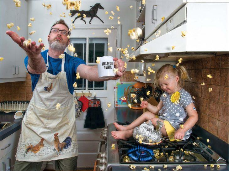 hombre cocinando palomitas con una niña en la estufa