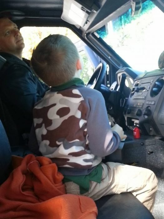 niño arriba de un camión de bomberos