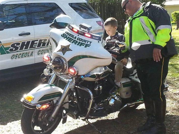 niño con autismo en una moto de policía