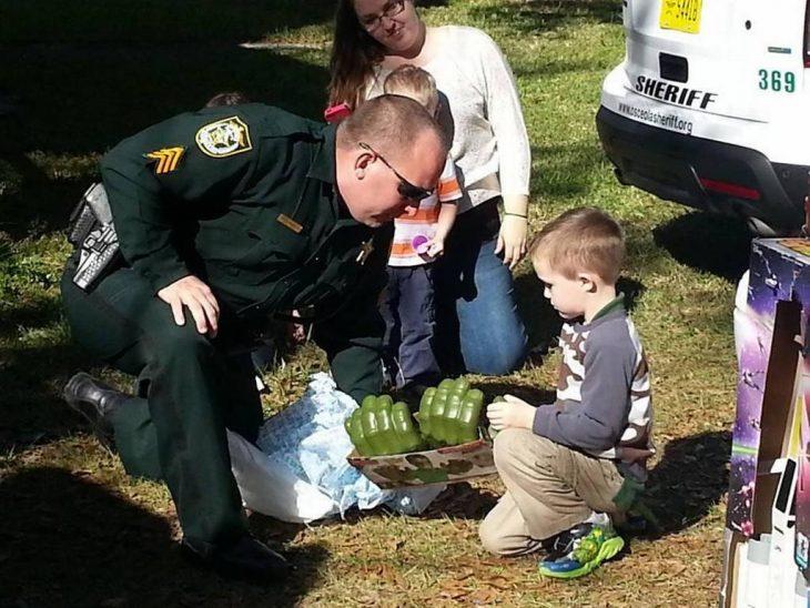 policía llevando juguetes a un niño con autismo