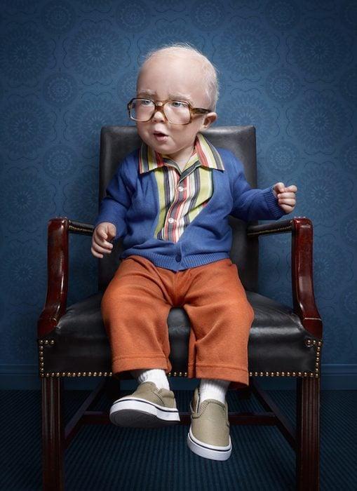 niño sentado en una silla vestido de un hombre mayor