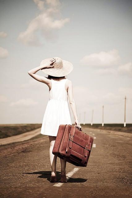 chica cargando una maleta y caminando por la carretera