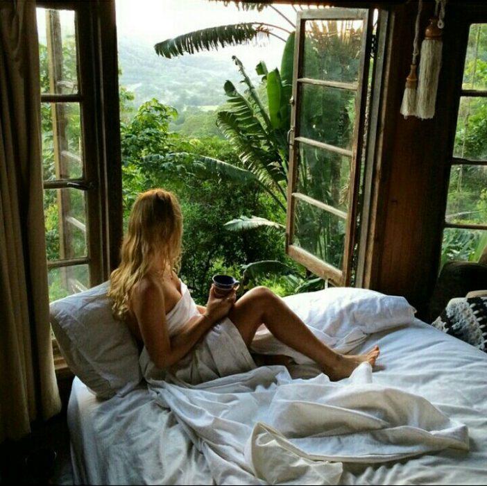 chica en la cama sentada tomando café mientras mira por una ventana