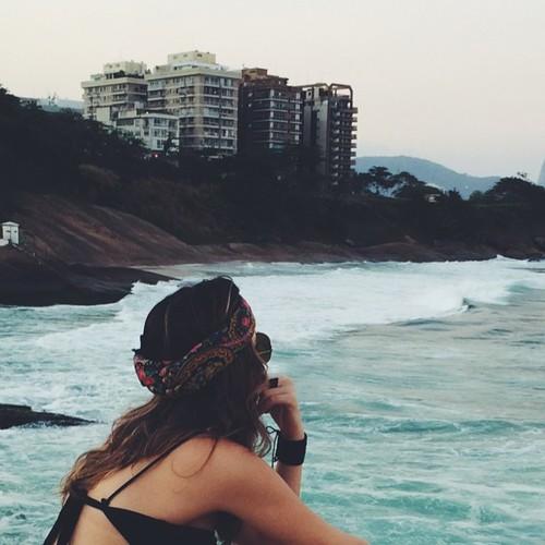 chica sentada junto a la playa viendo el mar