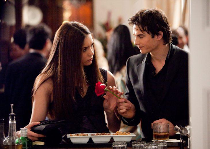 Escena de la serie the vampire diares elena y damon hablando en una fiesta