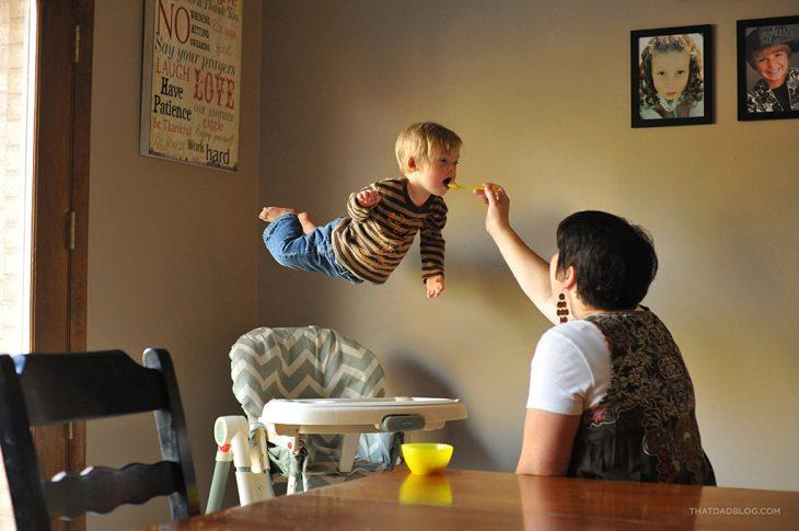 mamá dándole de comer a su hijo sentado en una periquera