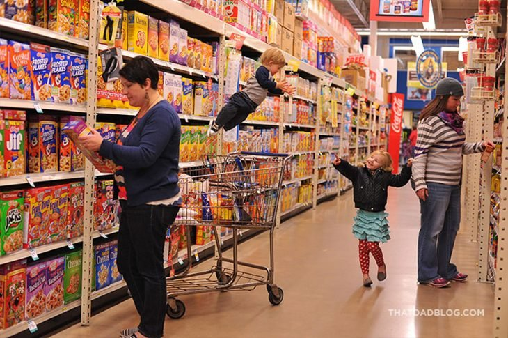 niño con síndrome de down que simula volar mientras esta con su mamá en el supermercado