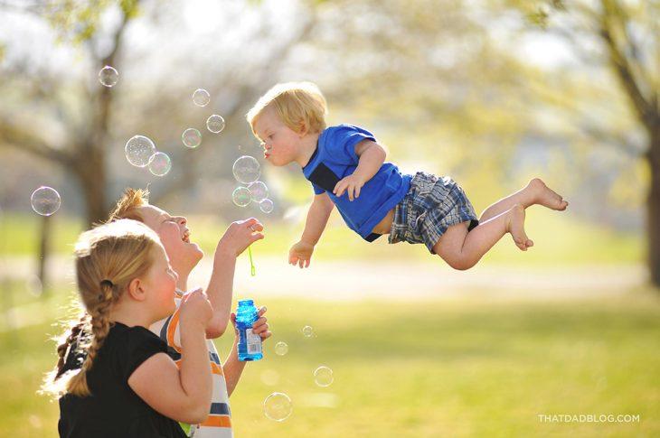 niño que simula volar sobre las personas mientras hace bombas de jabón