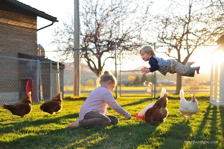niño volando sobre otros mientras juega con unas gallinas