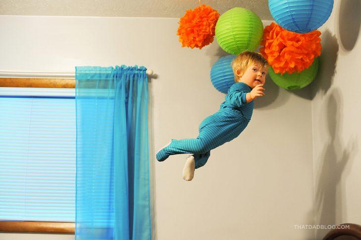 niño que simula volar en su habitación