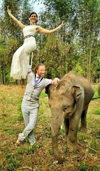 novio cargando a la novia en una mano y posando parados junto a un elefante