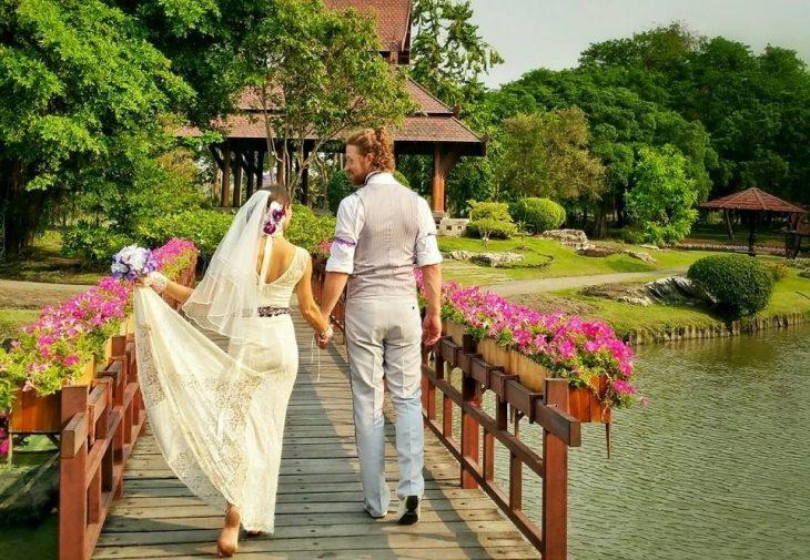 pareja de novios tomados de la mano caminando por un  puente