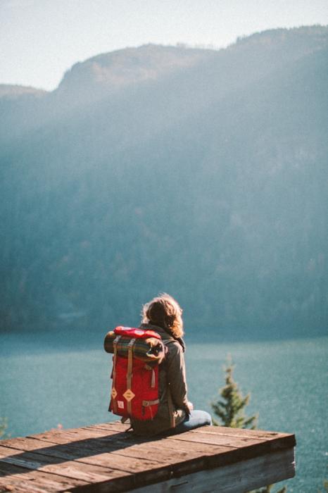 chica sentada en una montaña viendo hacia el mar