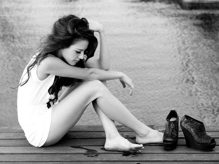 chica sentada en un muelle junto a un lago