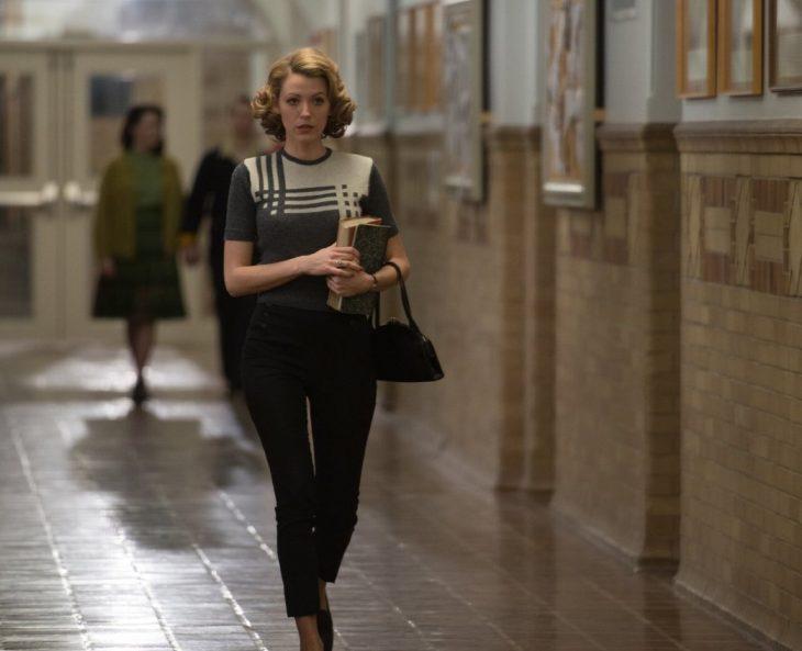 chica con libros en la mano  caminando por un pasillo