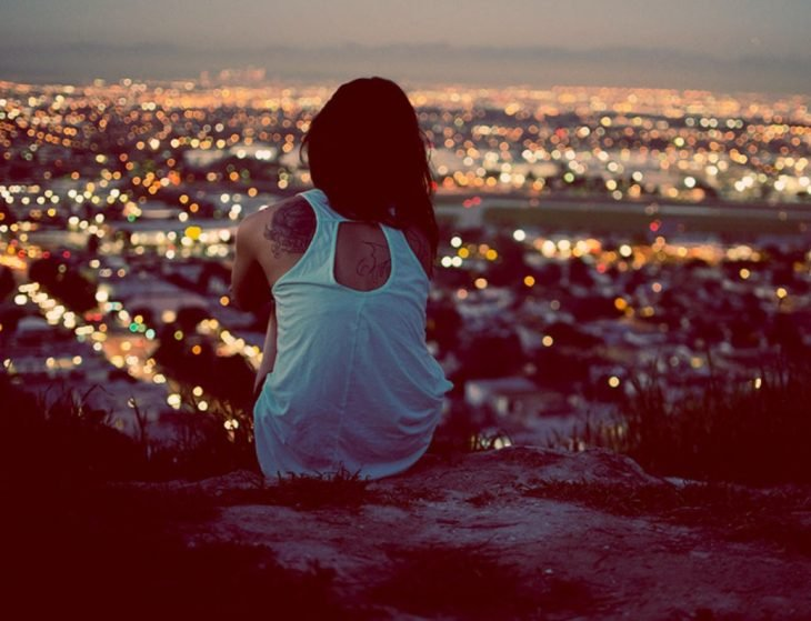 chica sentada mirando la ciudad