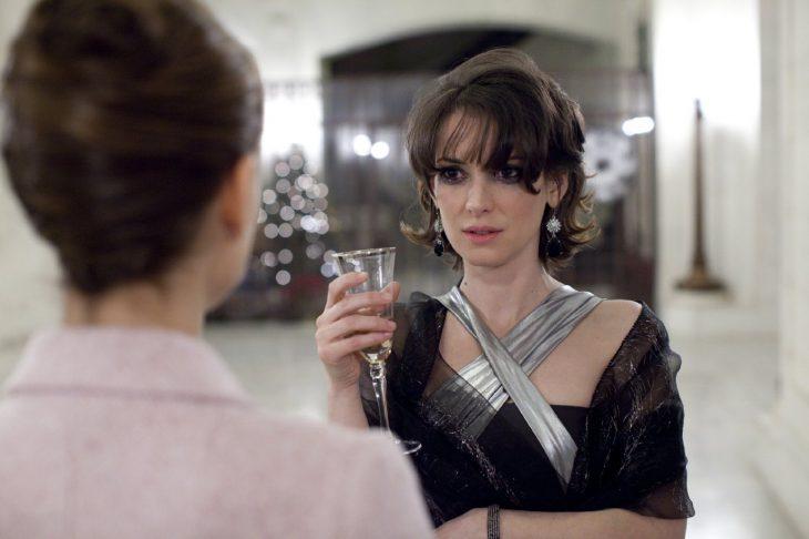 chica  con el maquillaje corrido tomando una copa de vino mientras habla frente a frente con otra