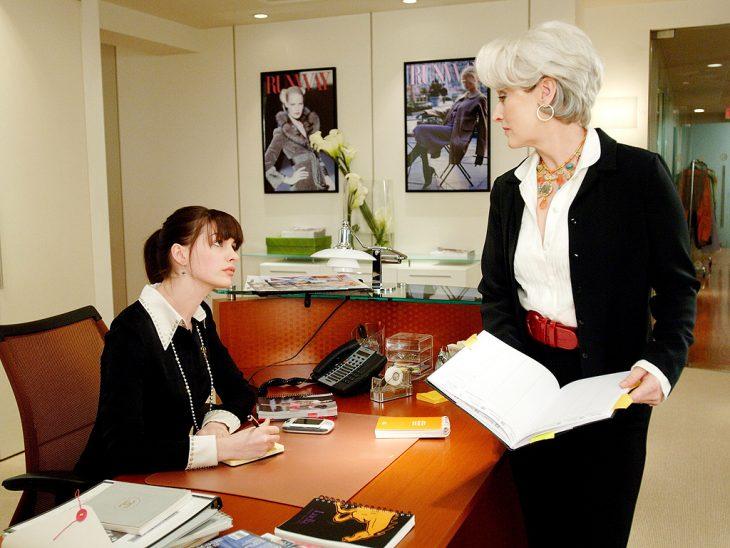 escena de la película el diablo viste a la moda protagonistas hablando en una oficina