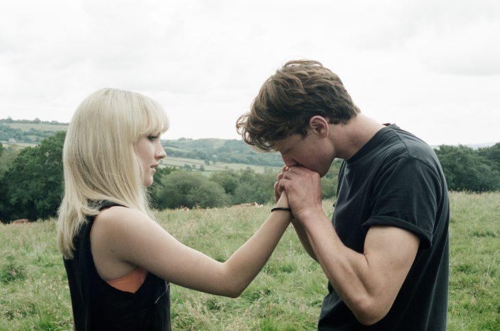 Chico besando la mano de una chica rubia parada en medio de un jardín
