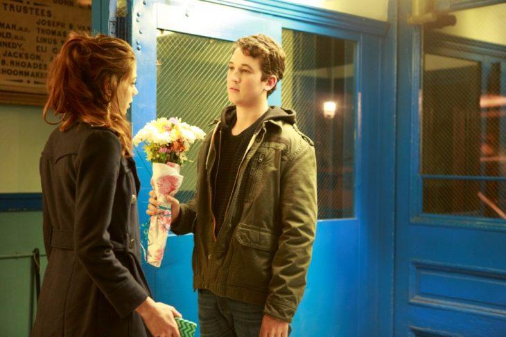 chico entregandole unas flores a una chica