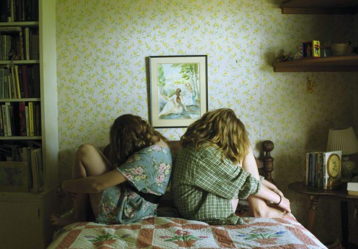 amigas sentadas en la cama con las piernas flexionadas