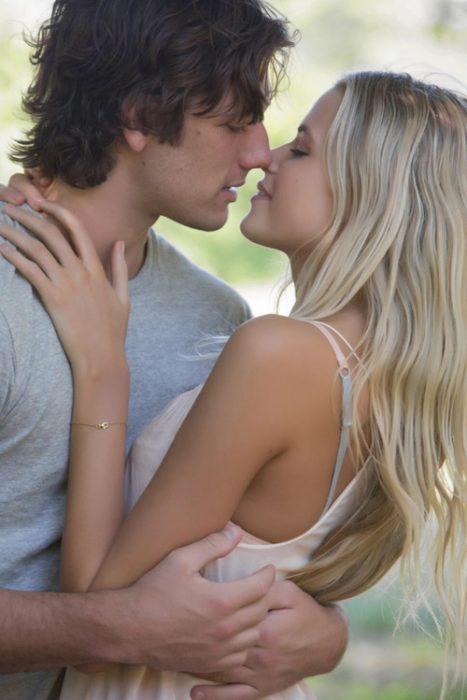 pareja de novios abrazados y besándose