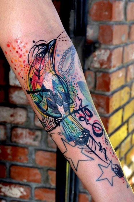 pájaro a colores tatuado al estilo acuarela