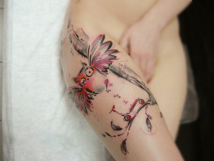 Búho tatuado en una pierna al estilo acuarela