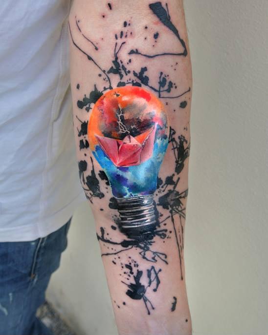 barco dentro de un foco tatuado con la técnica de acuarela