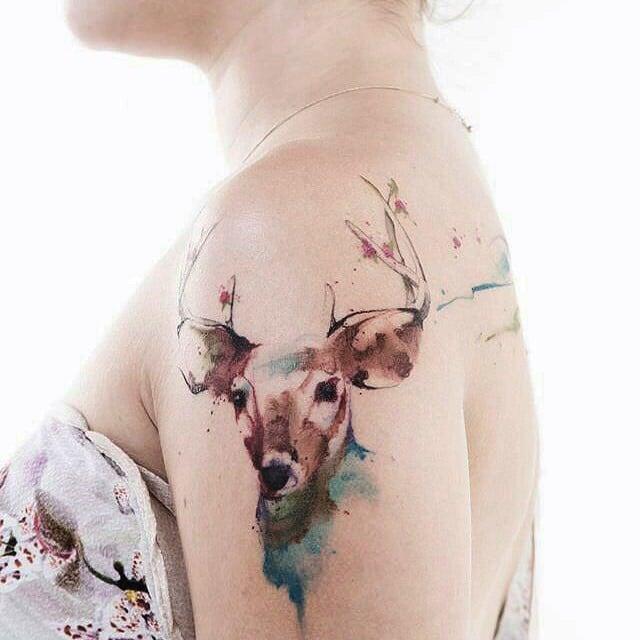 Venado tatuado en el brazo con la técnica acuarela