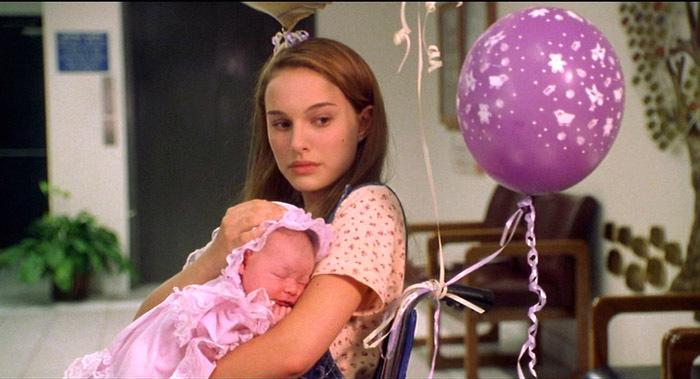 chica sosteniendo a una bebé en sus brazos mientras están sentadas en un sofá