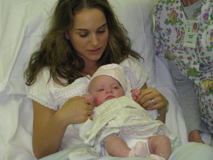 chica con un bebé en brazos recostada en la cama