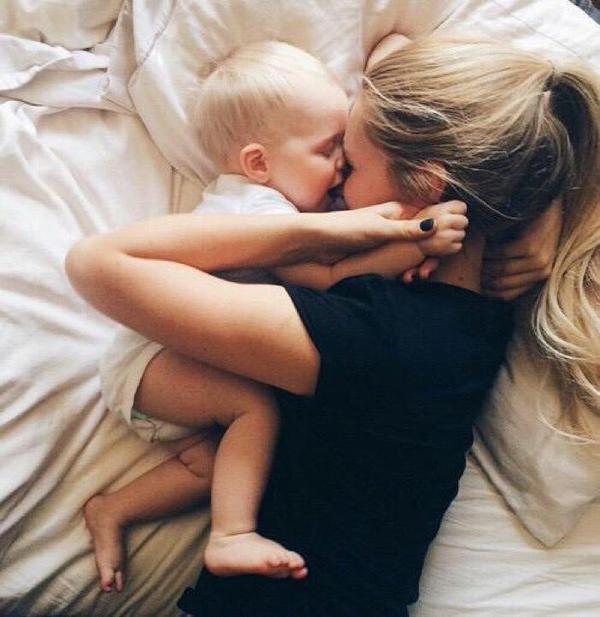 chica acostada junto a su bebé sonriendo