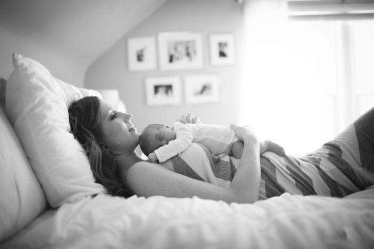 mujer recostada en una cama con un bebé sobre su pecho